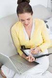 Woman using personal organizer and laptop at home Royalty Free Stock Photos