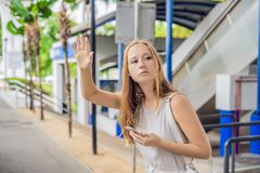 Woman using phone app for taxi ride hailing service or using phone app to find directions and guide during travel. Girl royalty free stock photos