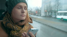 Woman using phone in bus on rainy day