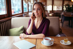 Woman using phone in cafe. Stock Image