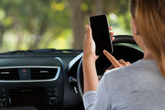 Woman using phone in car on road Stock Photos