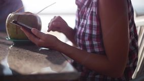 Woman using phone and drinking a cocktail from a coconut in the beach cafe, Close up. 1920x1080. Woman using phone and drinking a cocktail from a coconut in the stock video footage