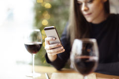 Woman using phone and drinking glass of red wine in cafe royalty free stock photography