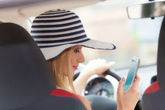 Woman using phone while driving her car Royalty Free Stock Photos