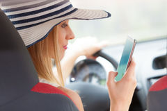 Woman using phone while driving her car Stock Photos