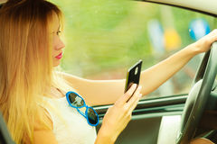 Woman using phone while driving her car Stock Image