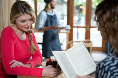 Woman using phone while friend reading book in coffee shop Stock Photo