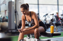 Woman using phone at gym. Young woman athlete using cell phone at gym. Latin woman in sportswear checking phone while resting after workout on bench. Beautiful Stock Image
