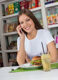Woman Using Phone While Having Snacks In Store Stock Image