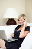 Woman using phone and laptop. Half body portrait of young woman on sofa talking on telephone with laptop computer stock images