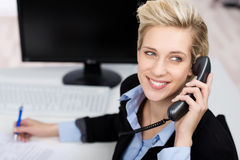 Woman Using Phone While Looking Up In Office. Closeup of happy young woman using phone while looking up in office stock photos