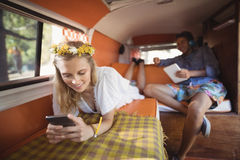 Woman using phone with man holding tablet in van Royalty Free Stock Image