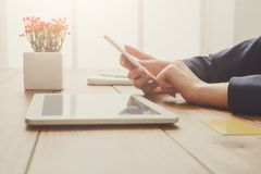 Woman`s using phone for payment with credit card. Woman using phone for online payment while sitting at wooden table, close-up, side view Stock Image