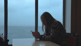 Woman using phone in ship cabin. Woman in sweater sitting at table in cabin of sailing contemporary ferryboat and browsing smartphone with view of cold sea stock video footage