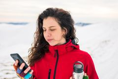 Woman using phone on a snow covered mountain royalty free stock photos