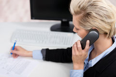 Woman Using Phone While Writing In Office Royalty Free Stock Images