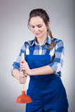 Woman using a plunger. Independent beautiful woman using  a plunger Stock Photography
