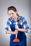 Woman using a plunger. During work, vertical Royalty Free Stock Photo