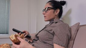 Woman using remote control and eating bun. In room stock footage