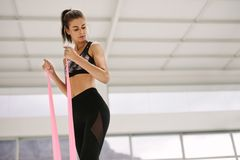 Woman using resistance band for arms exercise. Fit woman using resistance band for arms exercise at gym. Caucasian female working out with elastic bands at Royalty Free Stock Image