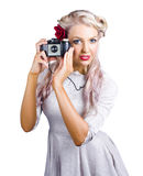 Woman using retro film camera. Attractive blond woman in pale mauve dress taking a picture with a retro film camera on white background Royalty Free Stock Photo