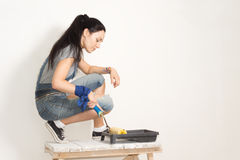 Woman using a roller to paint a wall royalty free stock images