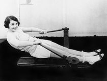 Woman using rowing machine Royalty Free Stock Image