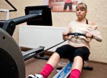 Woman using rowing machine. Young woman using rowing machine in gym stock photo