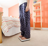 Woman Using Scale in Bedroom Stock Photo