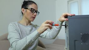 Woman using screwdriver near computer. In room stock footage