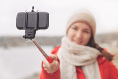 Woman using selfie stick taking photograph with cell phone Royalty Free Stock Images