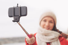 Woman using selfie stick taking photograph with cell phone Stock Images