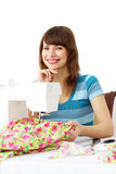 Woman using sewing machine. Seamstress using sewing machine to sew clothing royalty free stock photography