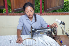 Woman using a sewing machine Stock Images