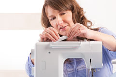 Woman using sewing machine Royalty Free Stock Photos