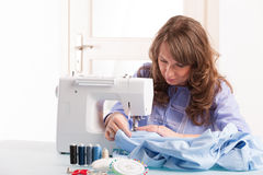 Woman using sewing machine Stock Photo
