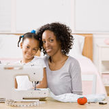Woman using sewing machine with daughter. Creative woman using sewing machine to sew clothing for daughter stock image