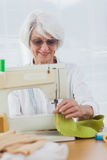 Woman using the sewing machine at home Stock Image