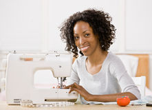 Woman using sewing machine to sew clothing Royalty Free Stock Photography