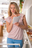 Woman using shopping list at grocery store. Shopping list - woman using shopping list at grocery store Stock Photo