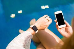 Woman using smart digital tech by the pool royalty free stock photo