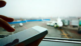Woman using smart phone at the airport. Close-up shot of a woman typing message on smart phone by the window at the airport, plane in background stock footage
