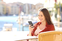 Woman using a smart phone in a bar on holidays Stock Photo