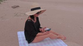 Woman using smart phone on the beach near sea. In summer day stock video