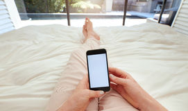 Woman using smart phone on bed Stock Photography