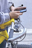 Woman using smart phone with bike Royalty Free Stock Images
