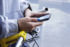 Woman using smart phone with bike Stock Images