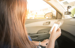 Woman Using a Smart Phone in car Stock Photography