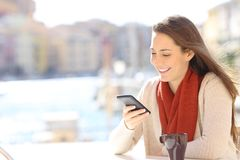 Woman using a smart phone in a coffee shop on vacation. Happy woman using a smart phone in a coffee shop on vacation in a coast town royalty free stock images