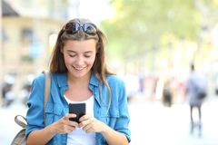 Woman using a smart phone with copy space. Front view portrait of a happy woman using a smart phone walking towards camera with copy space in the street Stock Photos